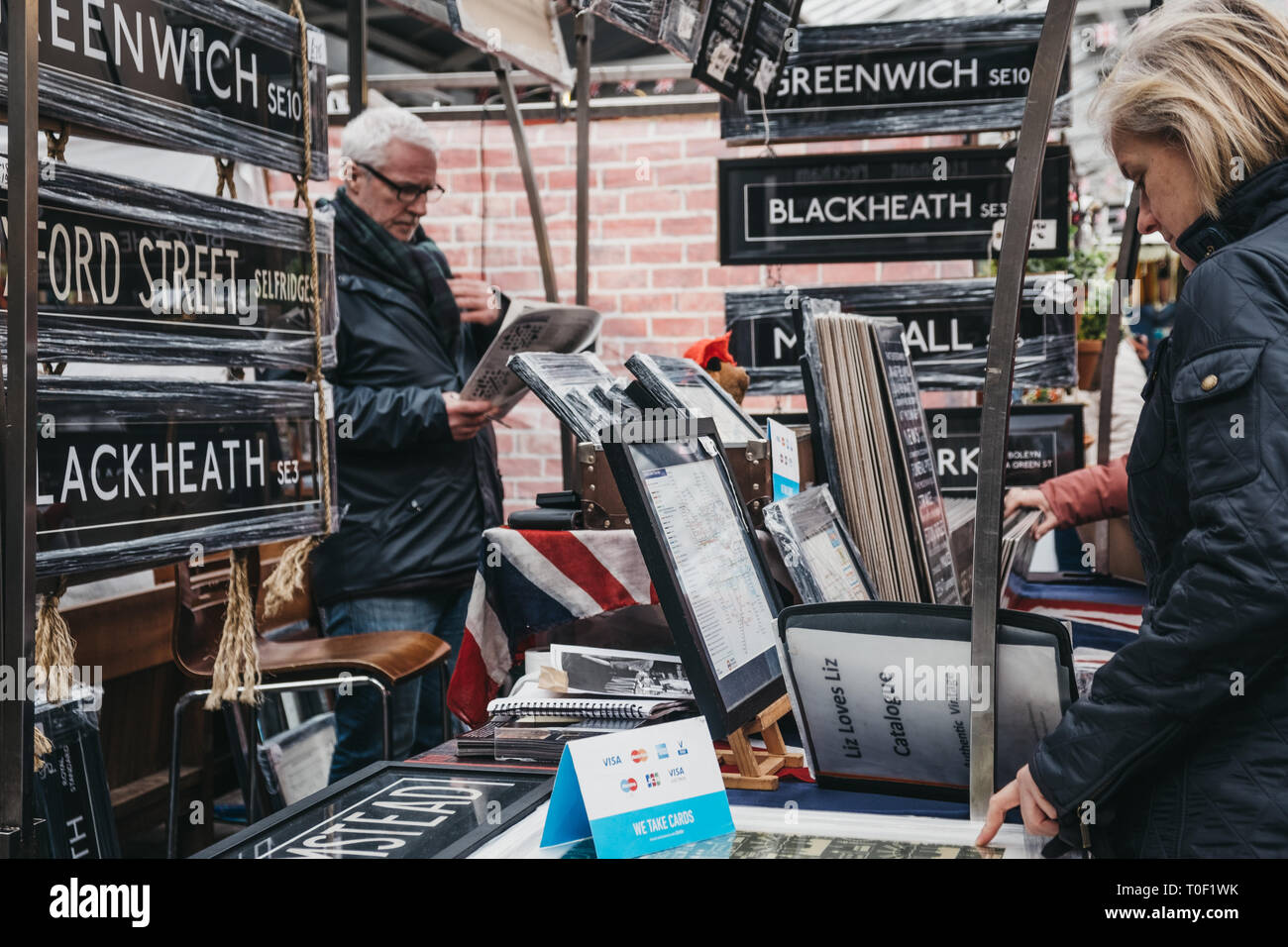 London, UK - March 16. 2019: People looking at posters and home decor on sale at a stall in Greenwich Market, London's only market set within a World  - Stock Image