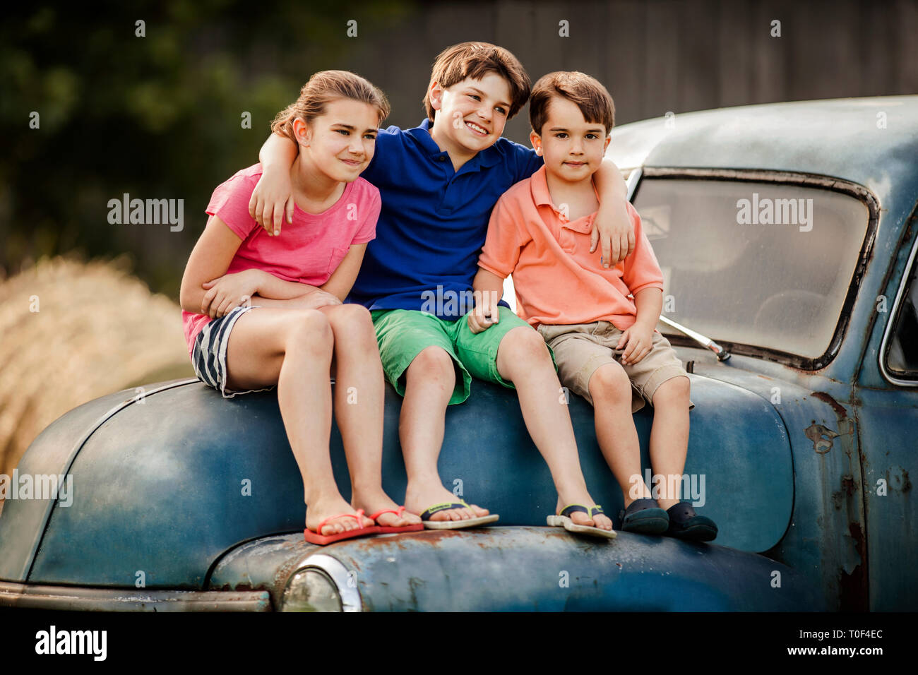 Portrait of three young siblings sitting together on an old car. - Stock Image