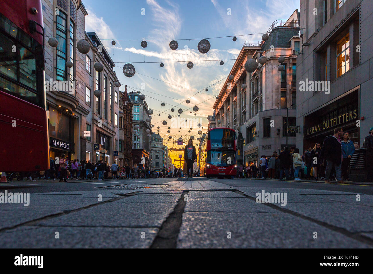 Regents Street, London. A low angled shot of the famous street, with a red London bus coming down approach and decorative lights hung across the road - Stock Image
