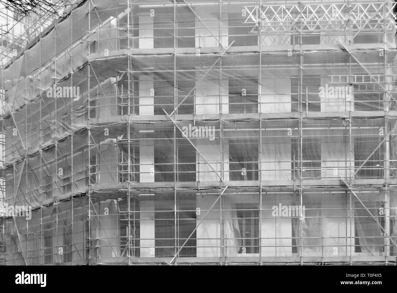 Protection net structure covering building on construction site, Black and white photography. - Stock Image