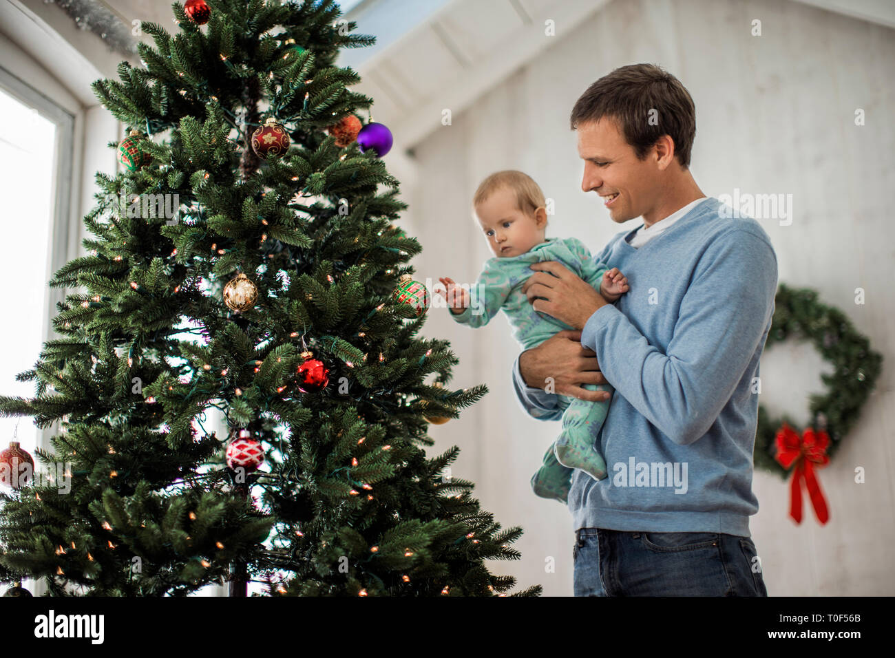 Happy father decorating a Christmas tree with his baby daughter. - Stock Image