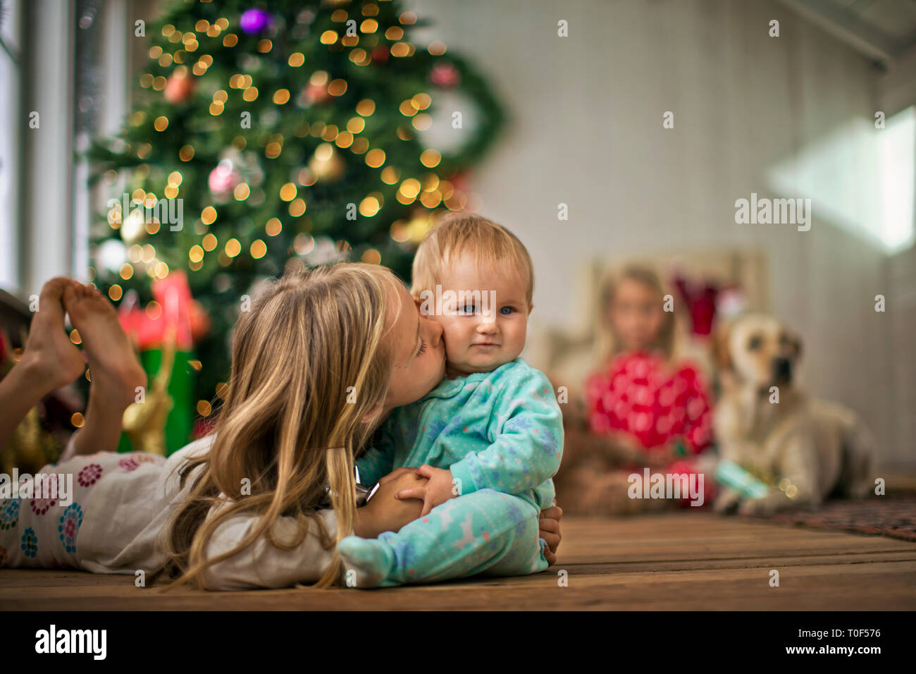 Young girl kissing her baby sister on the cheek. - Stock Image