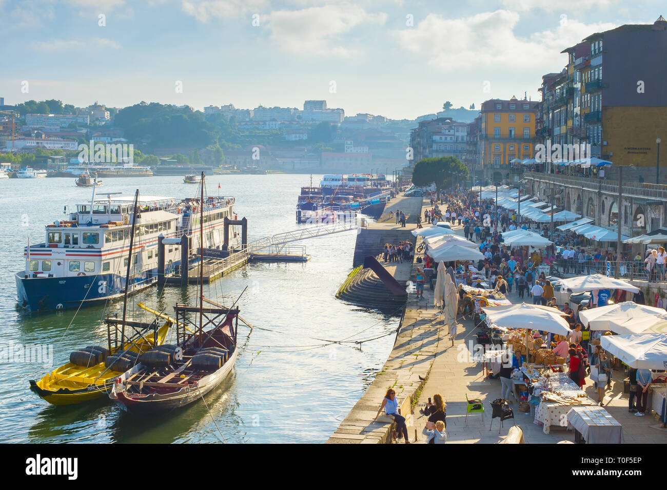 PORTO, PORTUGAL - JUNE 2, 2017: Cityscape with Porto Old Town quay, outdoor restaurants, souvenir stalls, crowd of tourists and tour boats moored by e - Stock Image