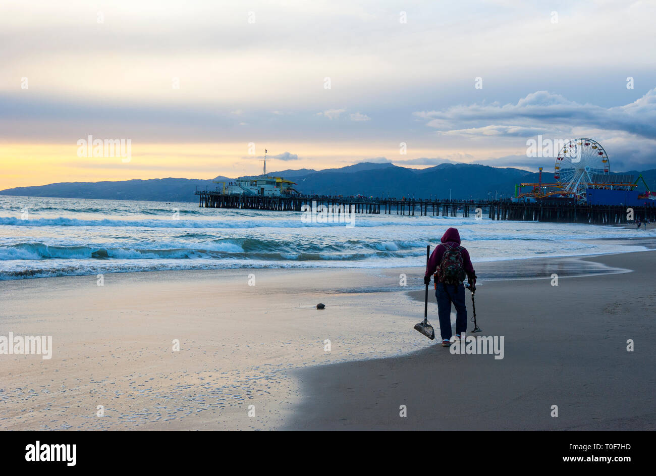 Prospector with metal detector looking for buried treasure at Santa Monica beach - Stock Image