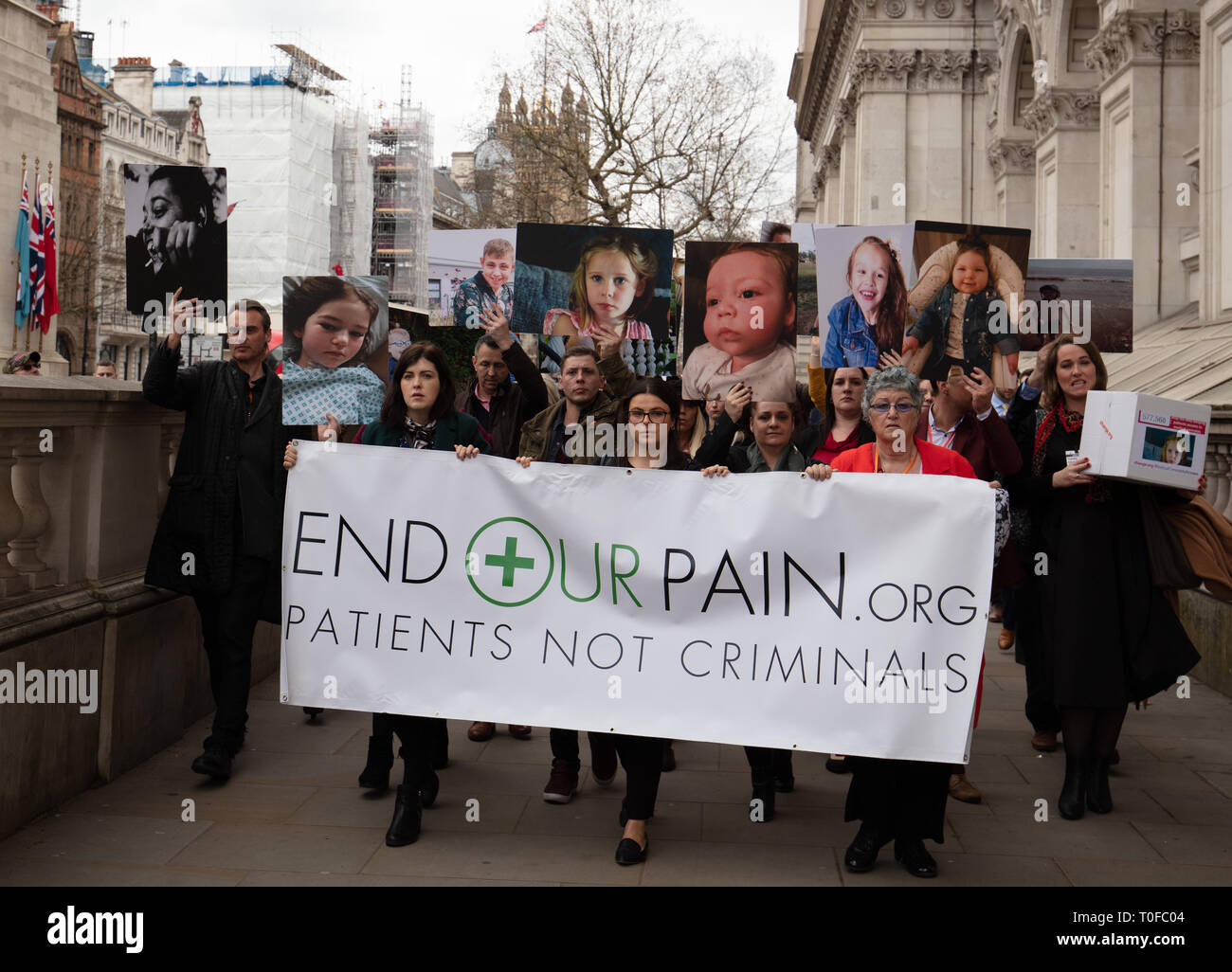 London, UK. 19th March, 2019. Members of the group End Our Pain, walk to 10 Downing Street, with images of their loved ones and deliver a petition with 577578 signatures in addition to a hundred Members of Parliament, for patient access of legalised medical cannabis. Credit: Joe Kuis / Alamy Live News - Stock Image