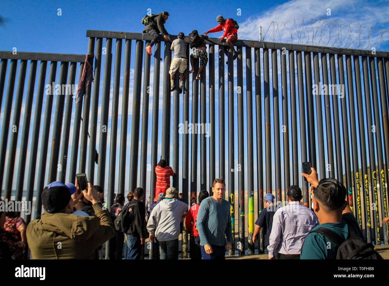 Baja California, Mexico. 19th Mar, 2019. Dozens of migrants try to enter the United States illegally from the Playas Tijuana area in the Mexican state of Baja California, Mexico, 19 March 2019. Around 16.00 local time (23.00 GMT), the migrants, almost a hundred according to the witnesses, arrived at the seashore in the Mexican town to try to jump the metal fence that in this area delimits the border between the two countries. EFE/Joebeth Terriquez Credit: EFE News Agency/Alamy Live News - Stock Image