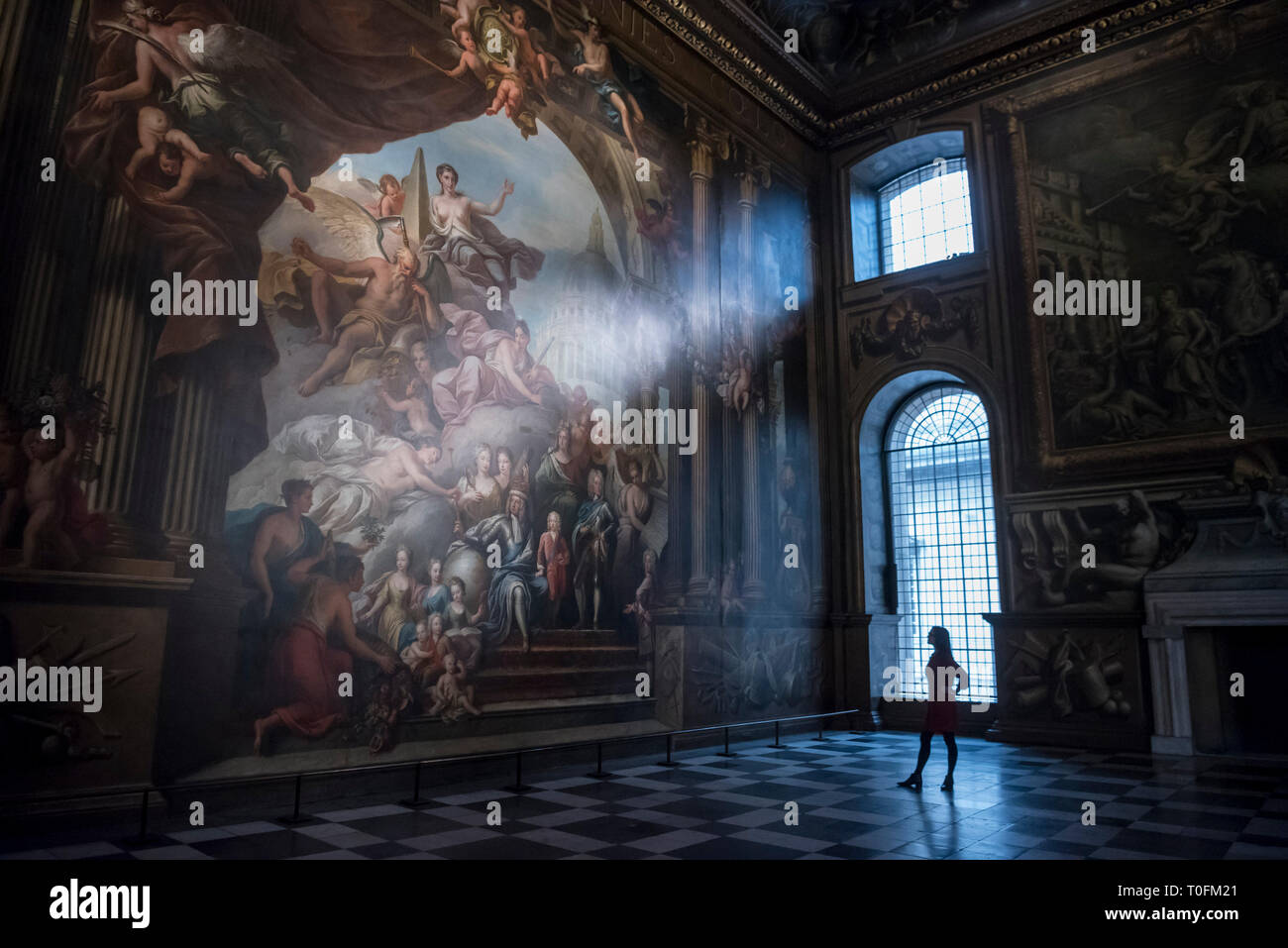 London, UK.  20 March 2019. A staff member poses during the unveiling of the newly restored Painted Hall at the Sir Christopher Wren designed Old Royal Naval College, Greenwich.  The Painted Hall reopens to the public on 23 March 2019 after a two-year National Lottery Funded conservation project which has brought its magnificent painted interior vividly back to life.  Painted by Sir James Thornhill, the first artist to be knighted, the vast 40,000 sq. ft decorated interior is a masterpiece of English baroque art.  Credit: Stephen Chung / Alamy Live News - Stock Image
