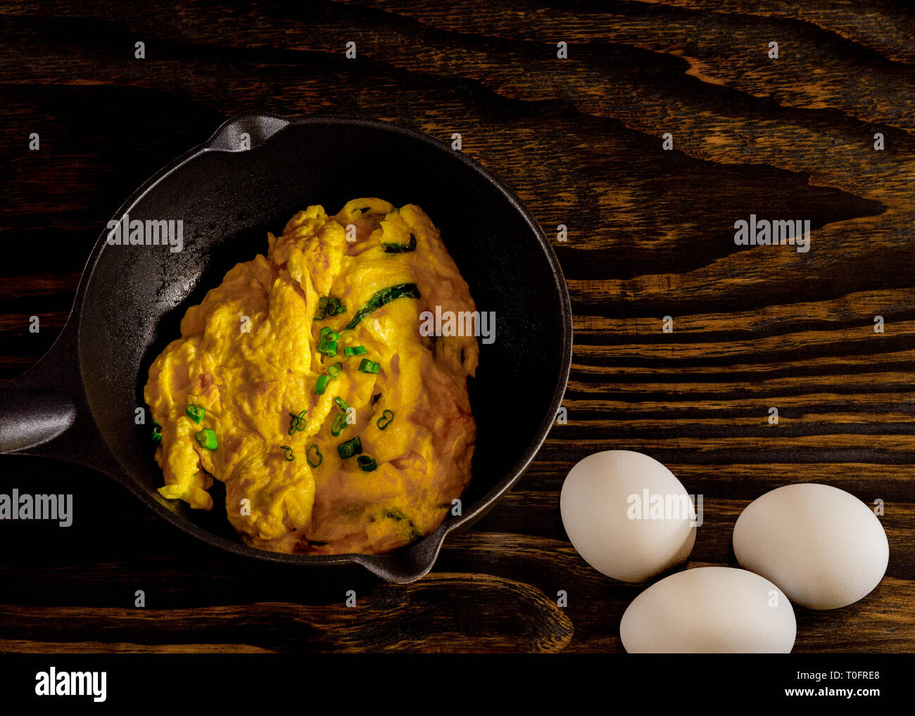 Omelet in frying pan with eggs, wood table background. - Stock Image