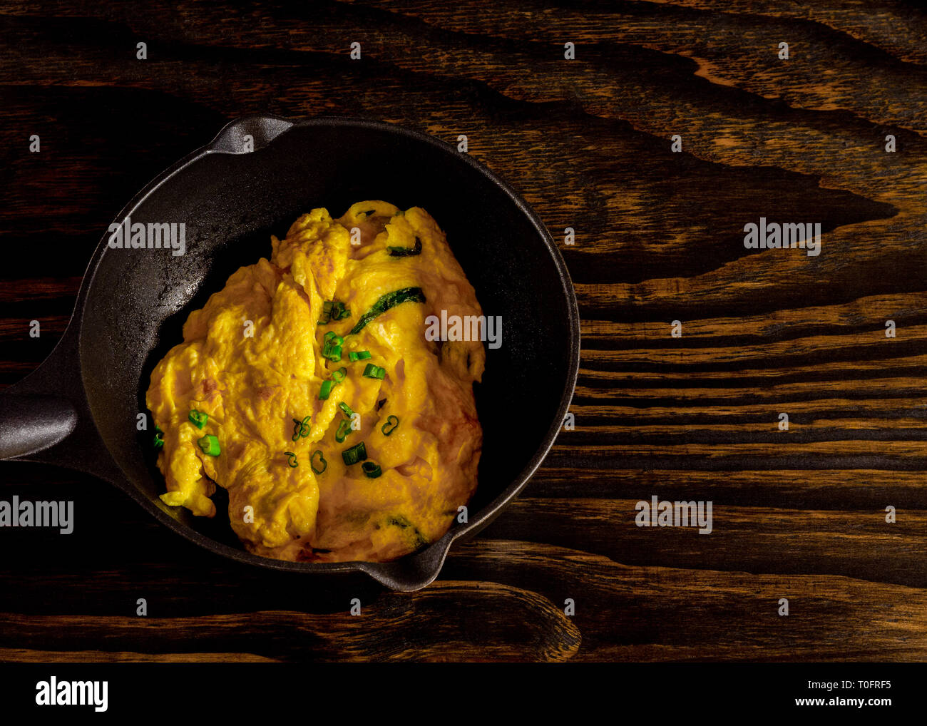 Scramble eggs, omblet, in pan. Eggs with spring onion. - Stock Image