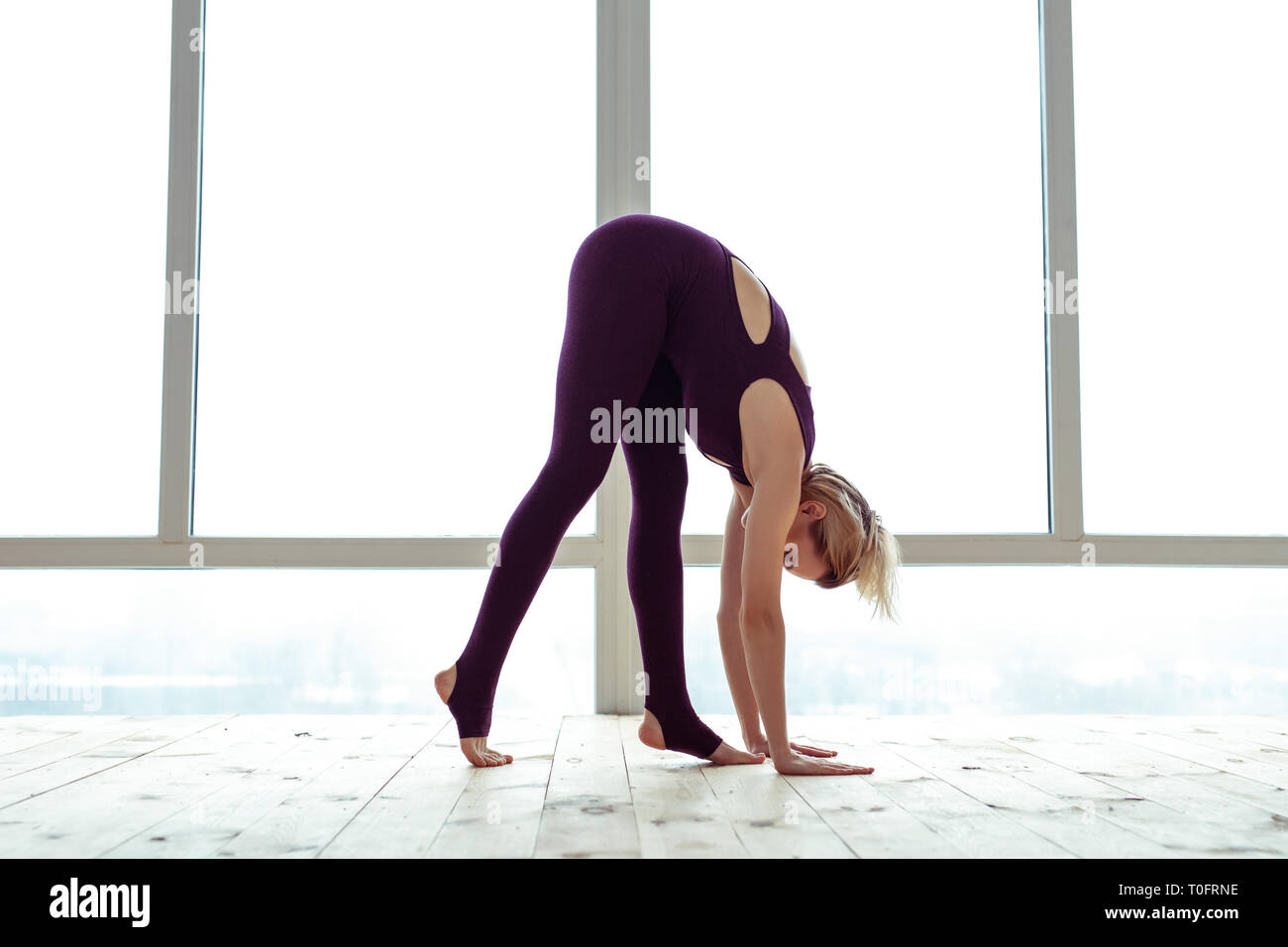 Hard-working young blonde lady in violet outfit bending over - Stock Image