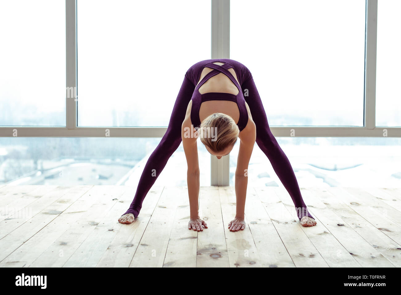Sportive fit lady bending over on city background - Stock Image