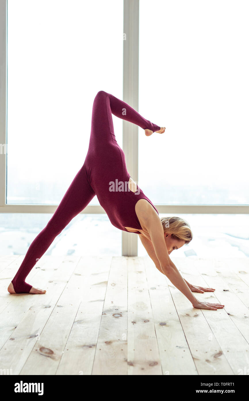 Blonde short-haired girl exercising on bare wooden floor and showing - Stock Image