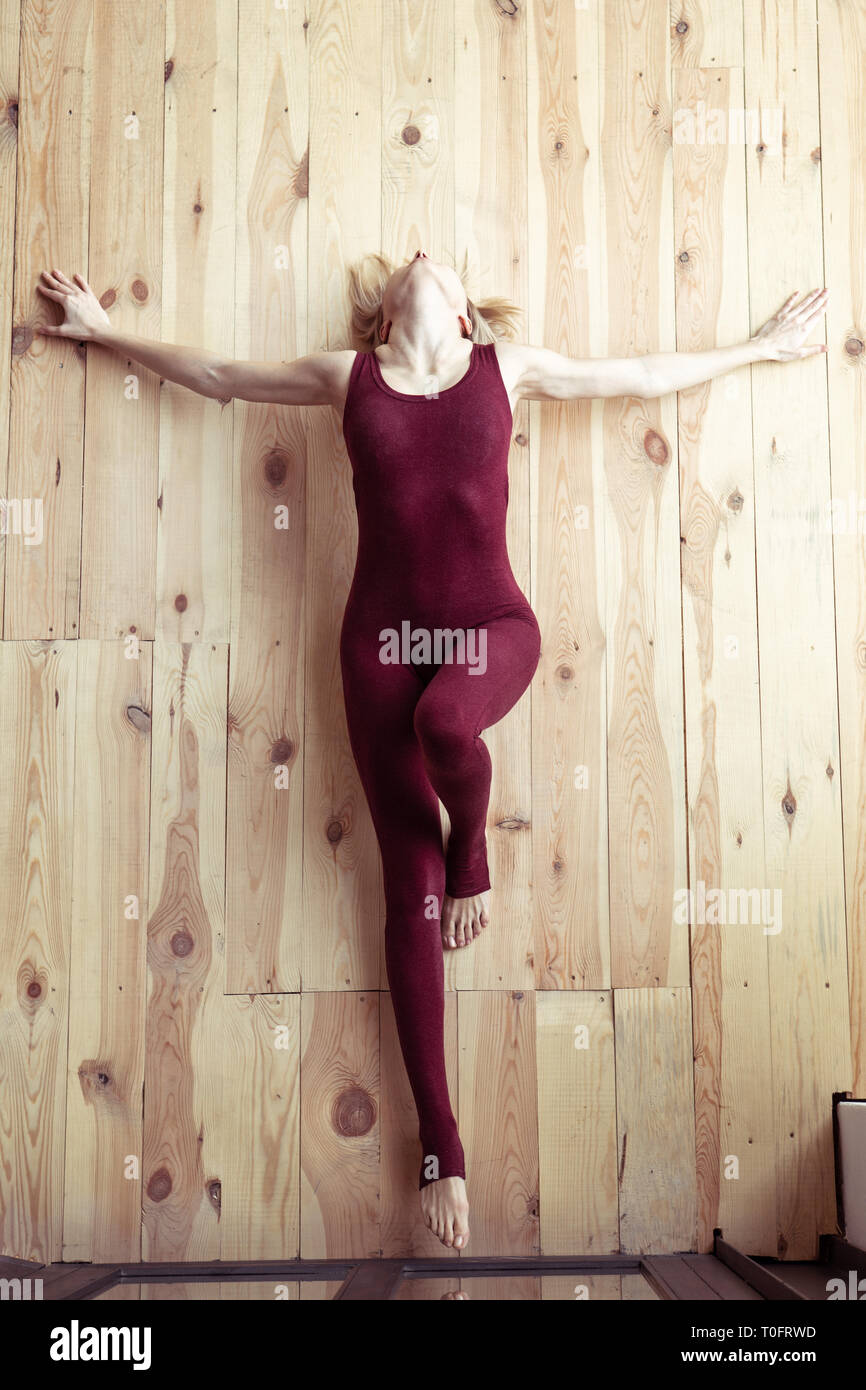 Skinny appealing girl in red fitting costume performing dramatic posture - Stock Image