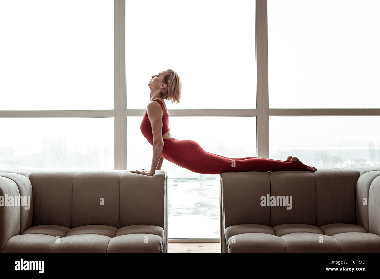 Appealing strong woman in bright red outfit performing yoga - Stock Image