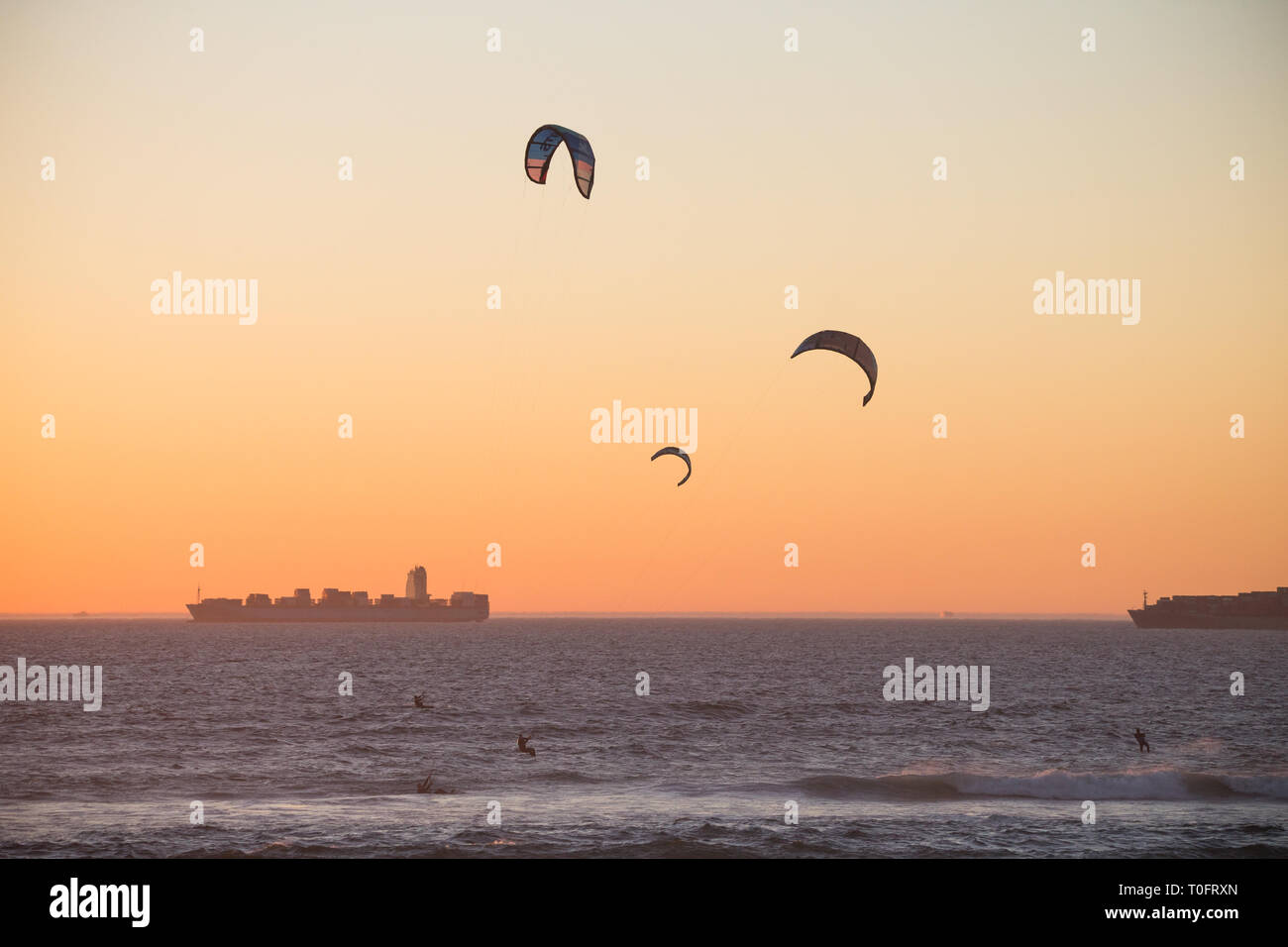 kitesurfers or kiteboarders silhouettes at sunset on the ocean with two tankers or ships in the background at Bloubergstrand, Cape Town, South Africa - Stock Image