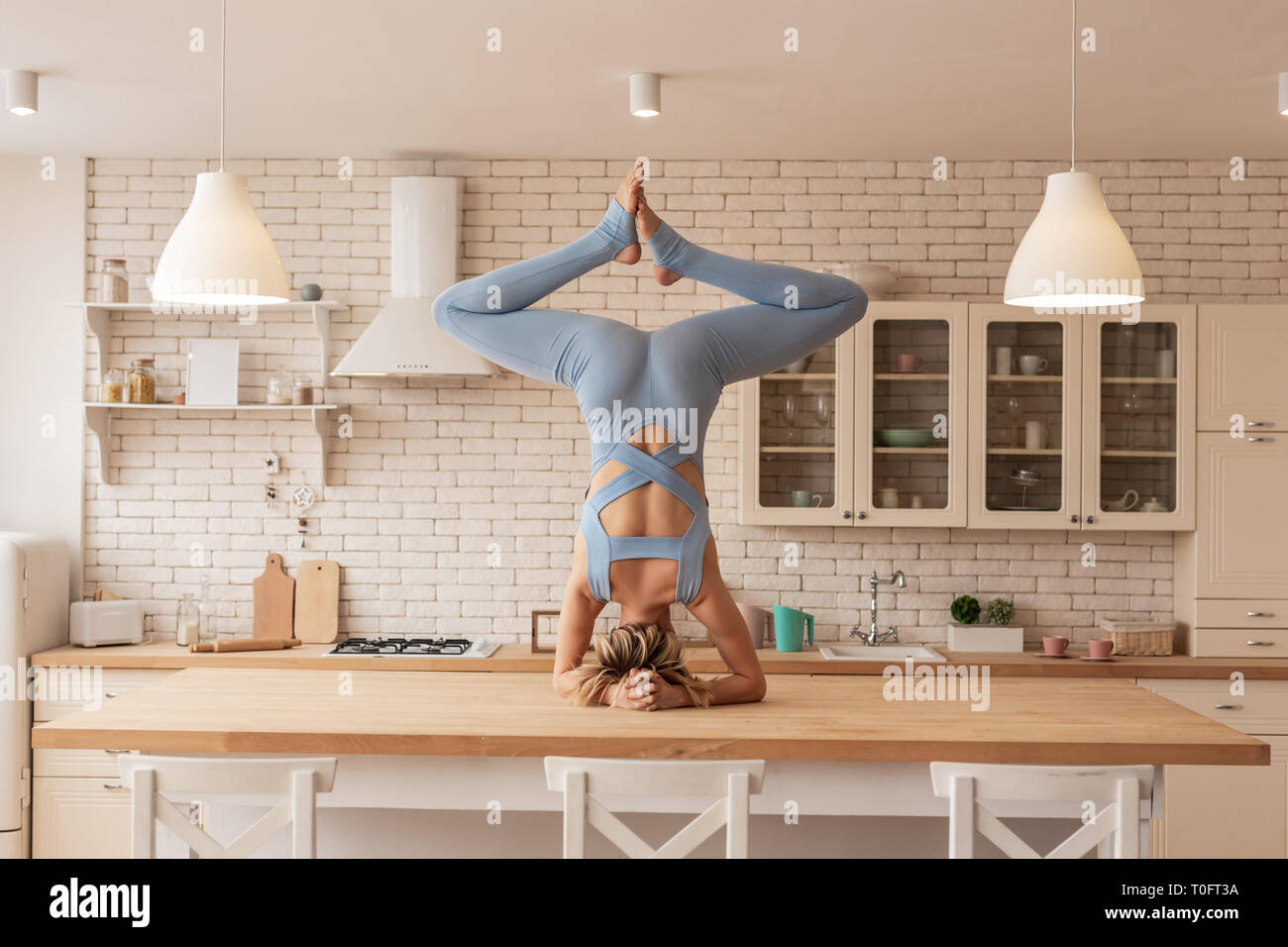 Flexible and strong young yoga master showing her outstanding skills - Stock Image