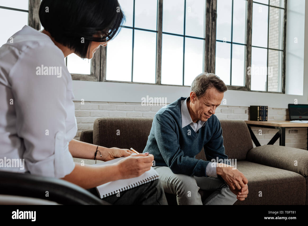 Distressed short-haired old man crying while being in depression - Stock Image