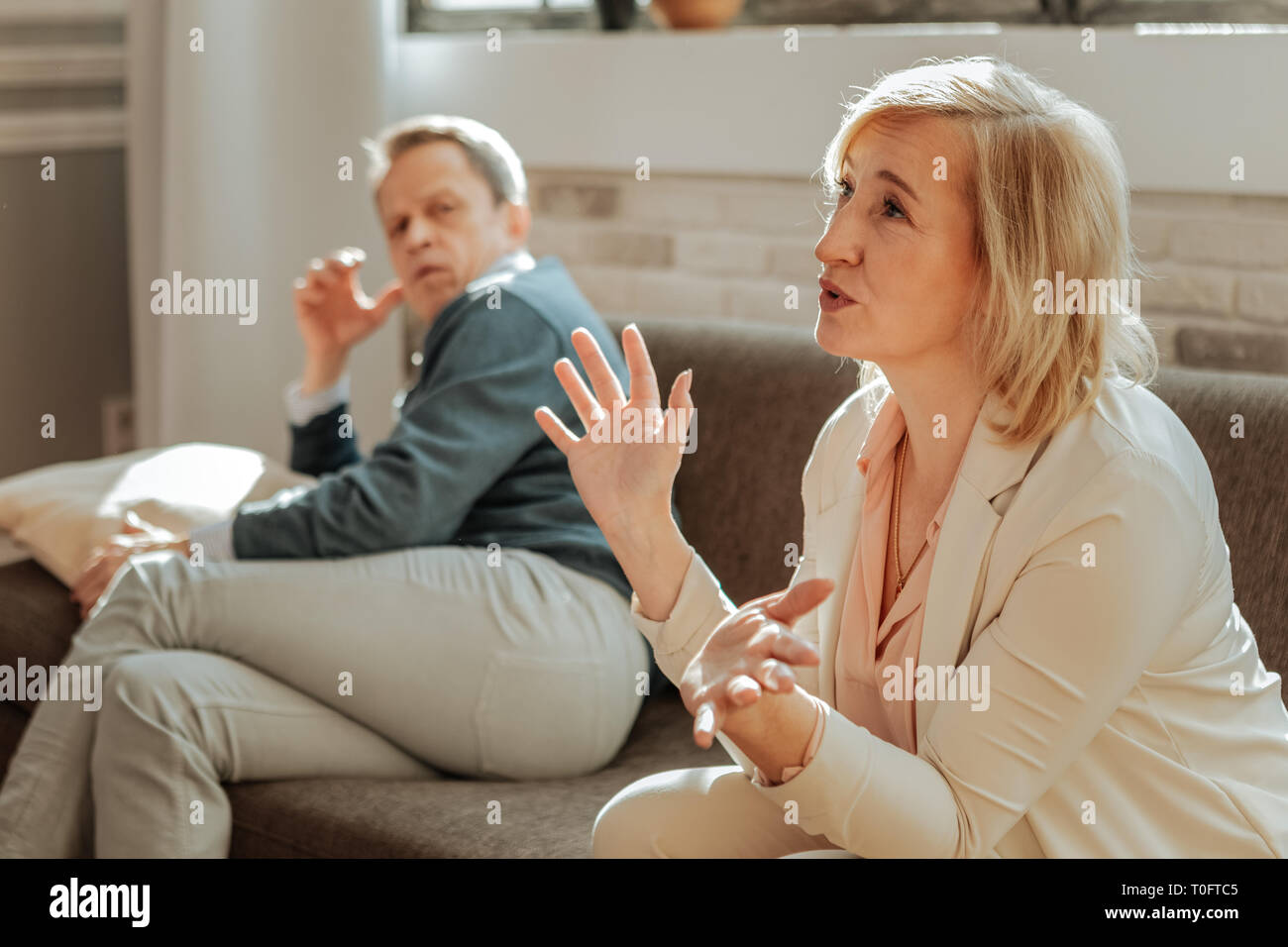 Expressive angry woman actively gesturing while explaining her discontentment - Stock Image