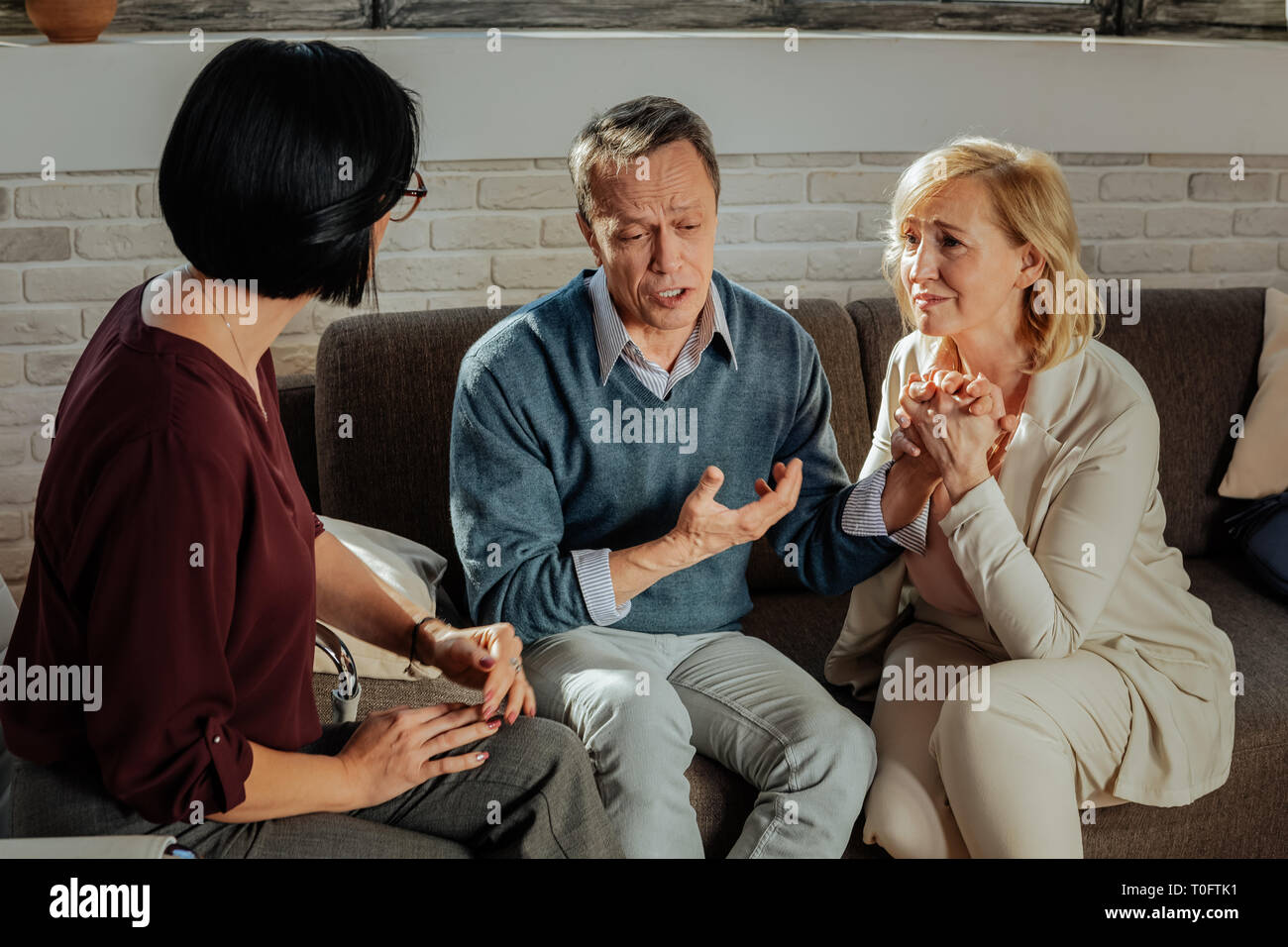 Depressed adult couple having conversation with personal therapist - Stock Image