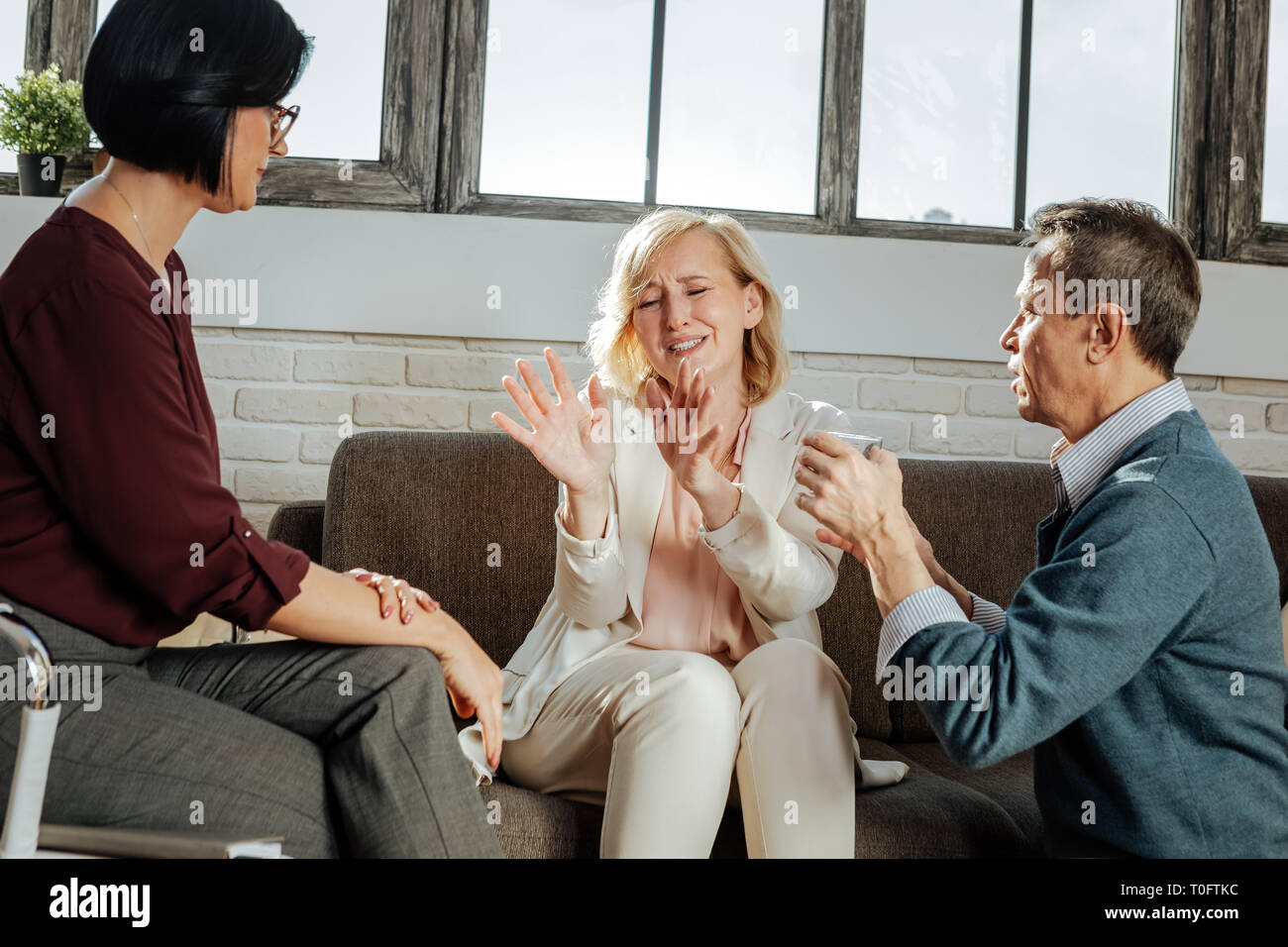 Upset and unhappy good-looking woman actively gesturing and explaining - Stock Image