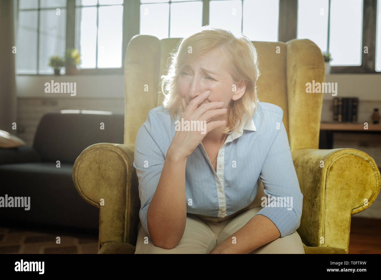 Dramatic old woman with blonde hair crying and sobbing - Stock Image