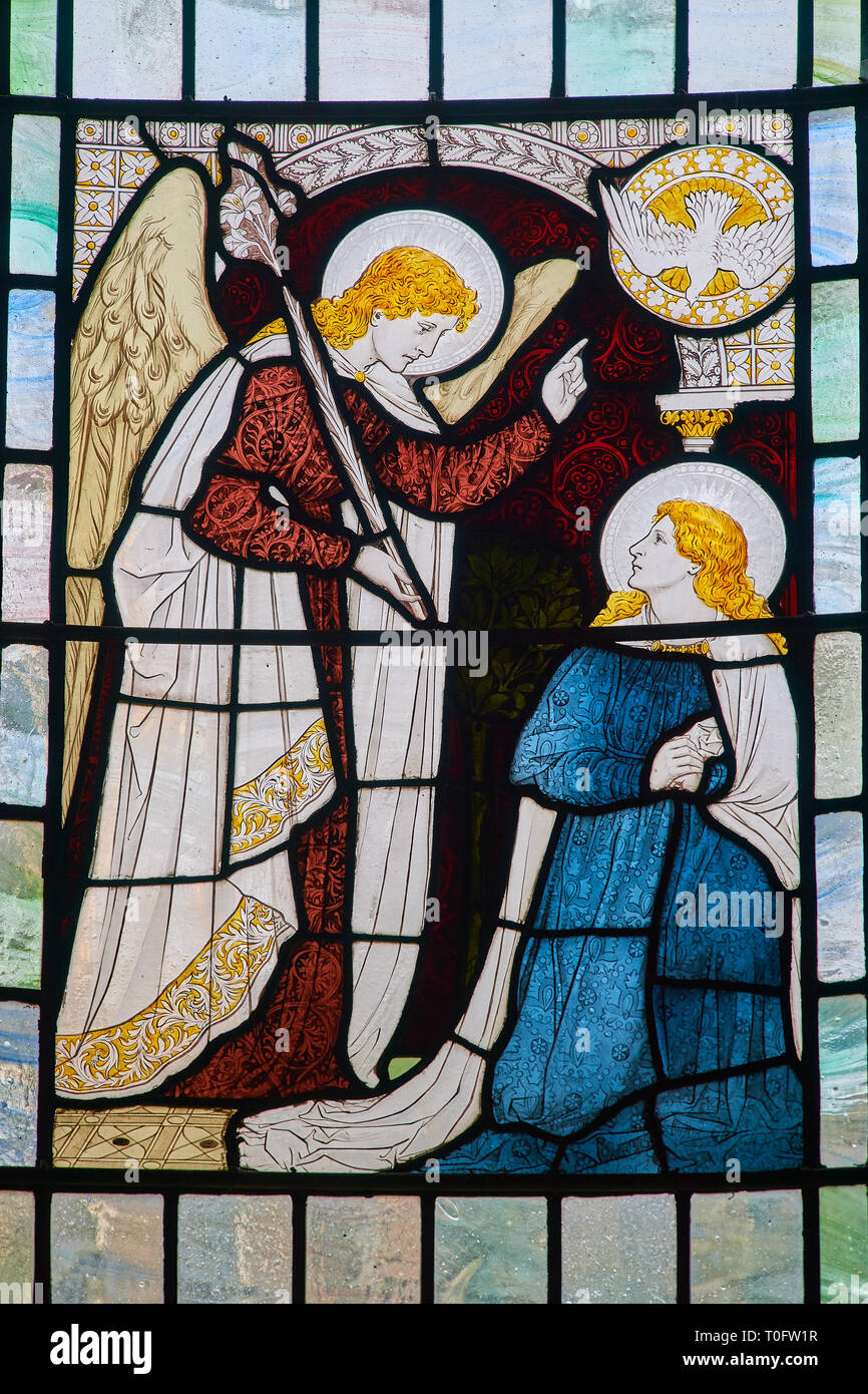 Stained glass window, in the chapel of Gonville & Caius college, university of Cambridge, England, of the angel Gabriel telling Mary she will conceive - Stock Image