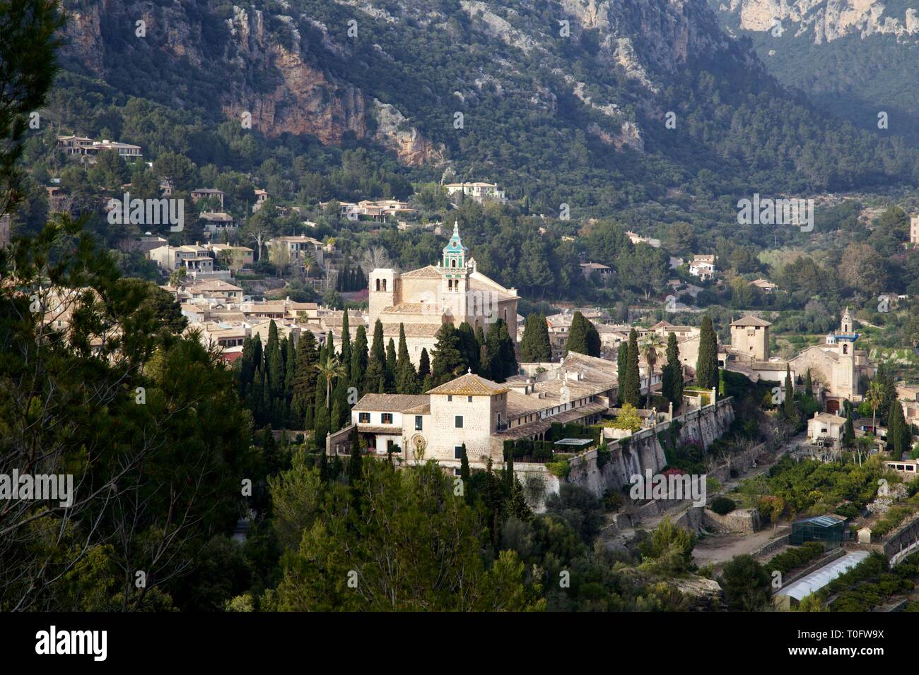 Panoramic view of the Spanish village of Valldemossa, Mallorca with the famous Cartuja Monastery nestled in the mountains on a sunny day - Stock Image