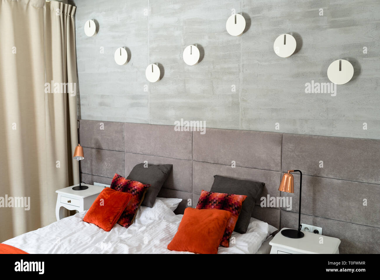 Bedroom with a large bed, orange pillows arranged in a row ...