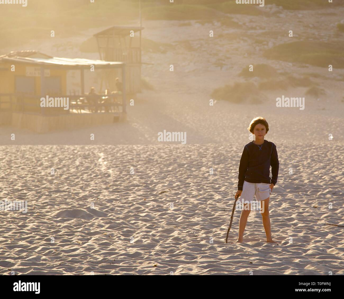 Young boy in front of rustic Beach Shack at Cala Torta, Mallorca at sunset - Stock Image