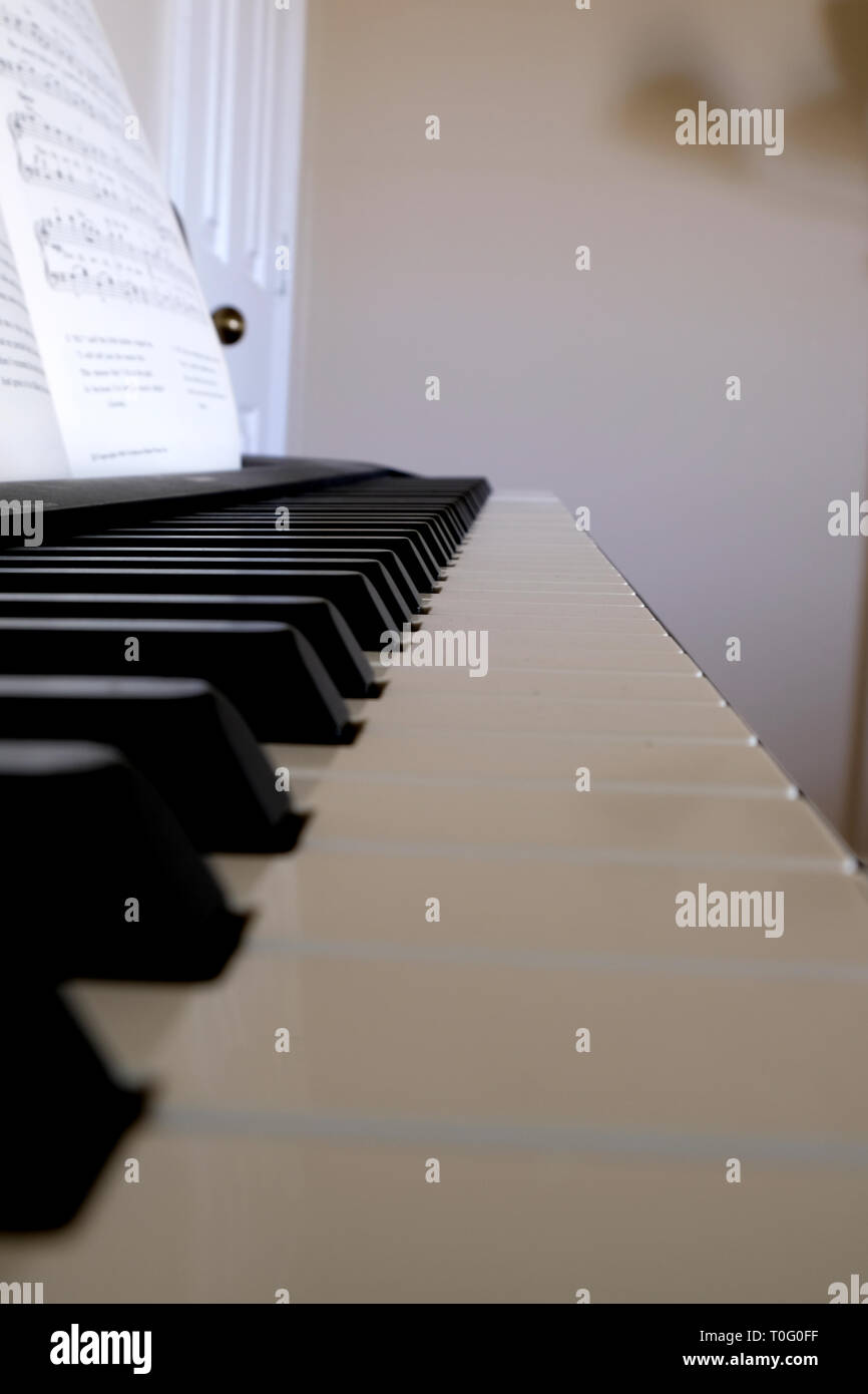 Electric piano keyboard fading into distance; piano keys up close. - Stock Image