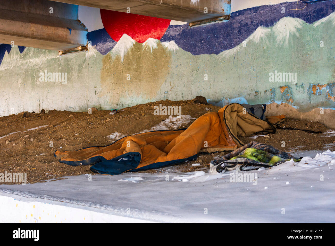 Homeless person's belongings and bedroll left in dirty highway underpass with drifted snow from recent snowfall, Castle Rock Colorado US. - Stock Image
