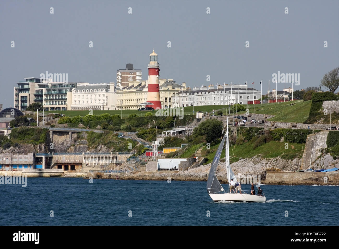A white yacht sails past Plymouth Hoe and Tinside. Swimming steps and Smeaton's Tower are in the active scene Stock Photo