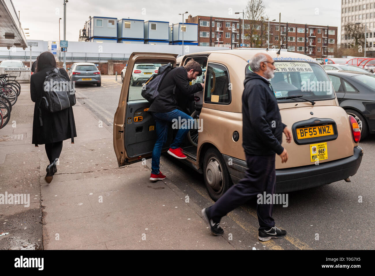 Man gets into a taxi outside Coventry Railway Station, Coventry, West Midlands, UK. - Stock Image