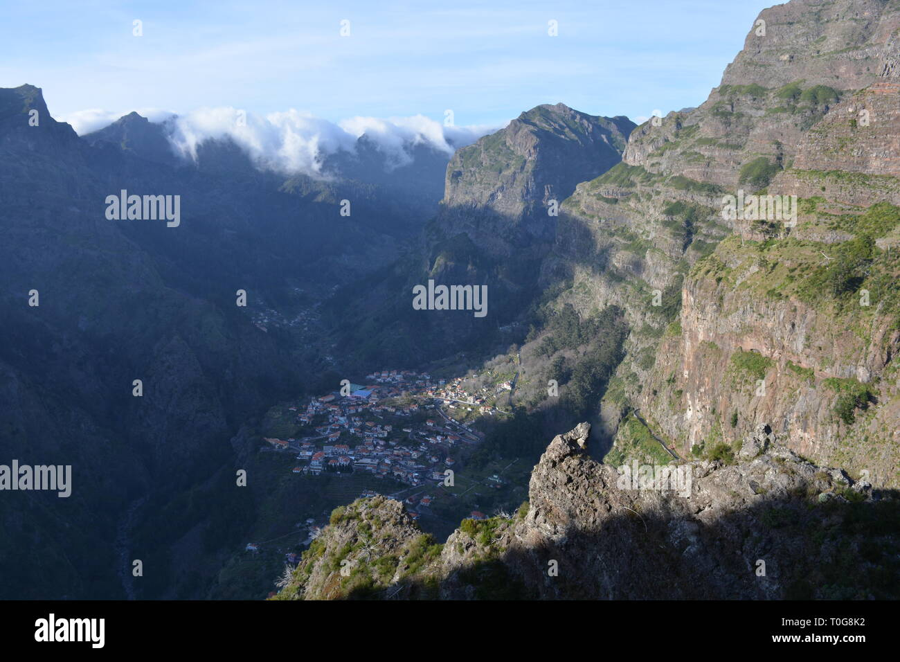Eira do Serrado looking to Curral das Freiras, a small town at the bottom of a valley surrounded by steep, cloud capped mountains, Madeira, Portugal - Stock Image