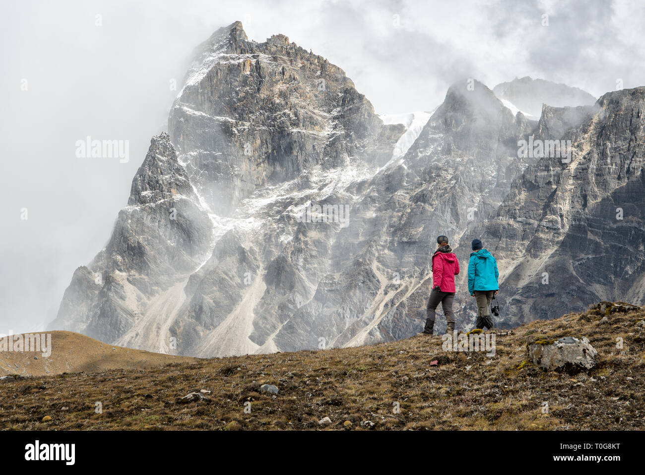 Two trekkers and mountains near Narethang, Gasa District, Snowman Trek, Bhutan - Stock Image