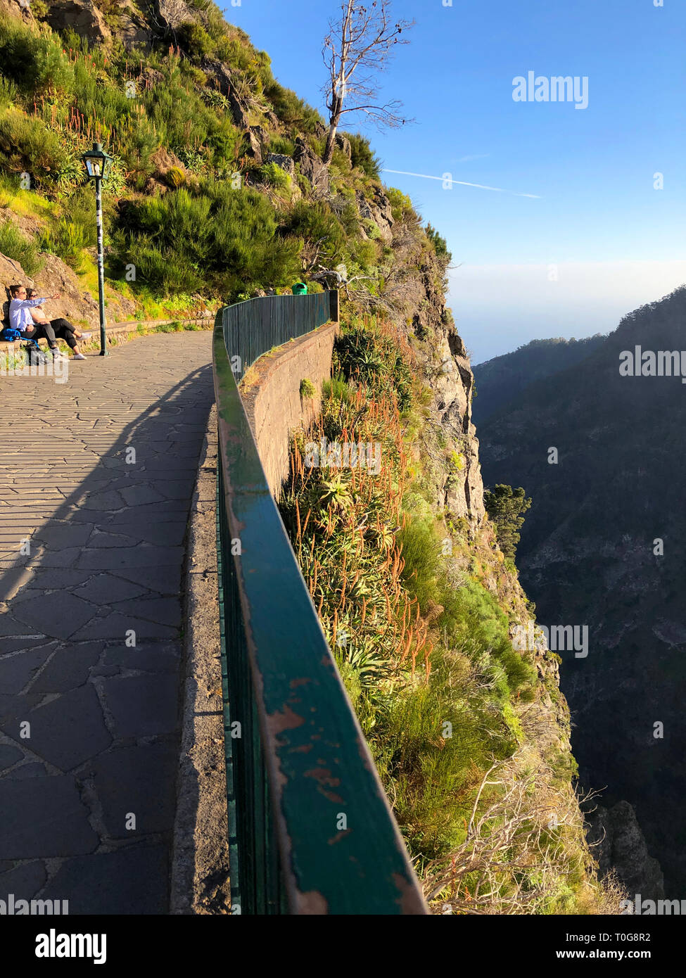 Tourists on a bench at the lookout point, admiring the dramatic mountain view in late afternoon sunlight, Miradouro da Eira do Serrado, Madeira / Port - Stock Image