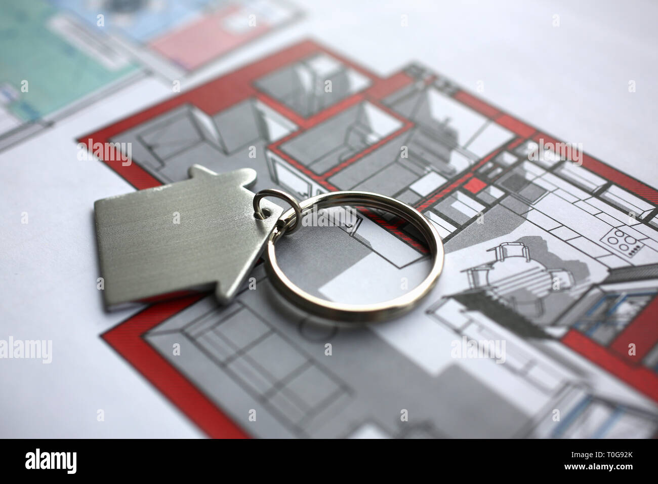 Metal key chain in form miniature house lies Stock Photo