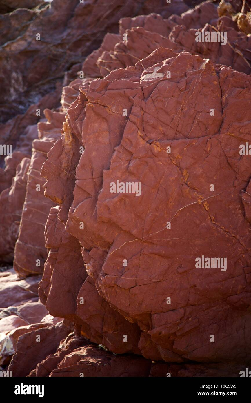 Geometric Red Rocks at the beach in Sun light, Puerto Valldemossa, Mallorca - Stock Image
