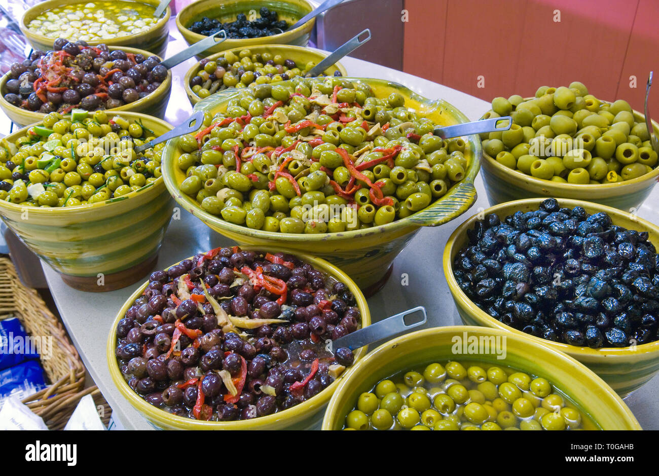 Lots of different types of olives for sale by weigh and displayed in
