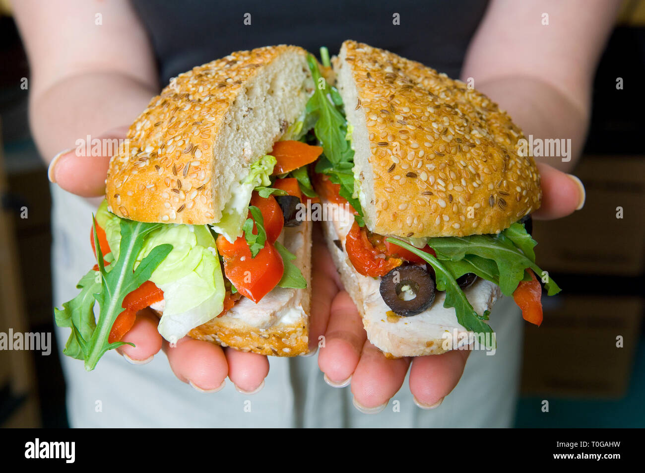 A delicious sandwich, roll, with lots of fresh ingredients, fillings. Stock Photo