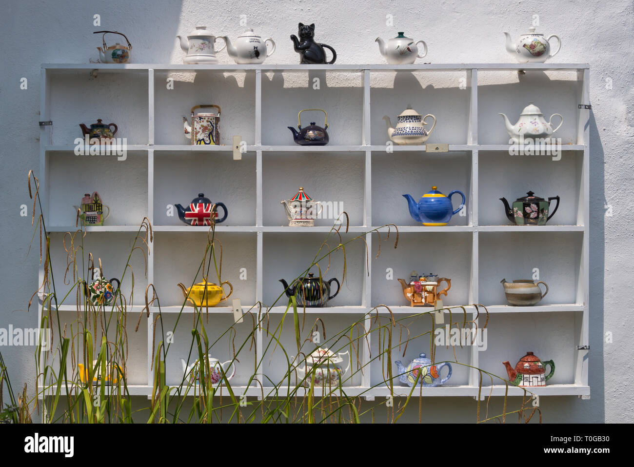 A collection of teapots on display outside a tea room on the Grand Western Canal in Tiverton, Devon, UK - Stock Image