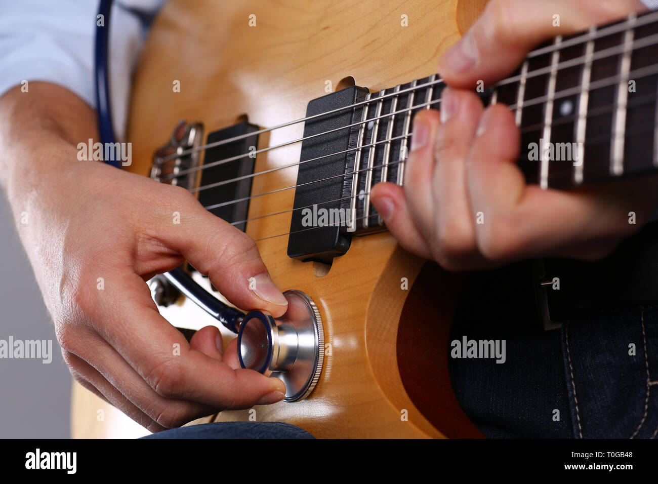Male arms hold stethoscope head diagnosing guitar - Stock Image