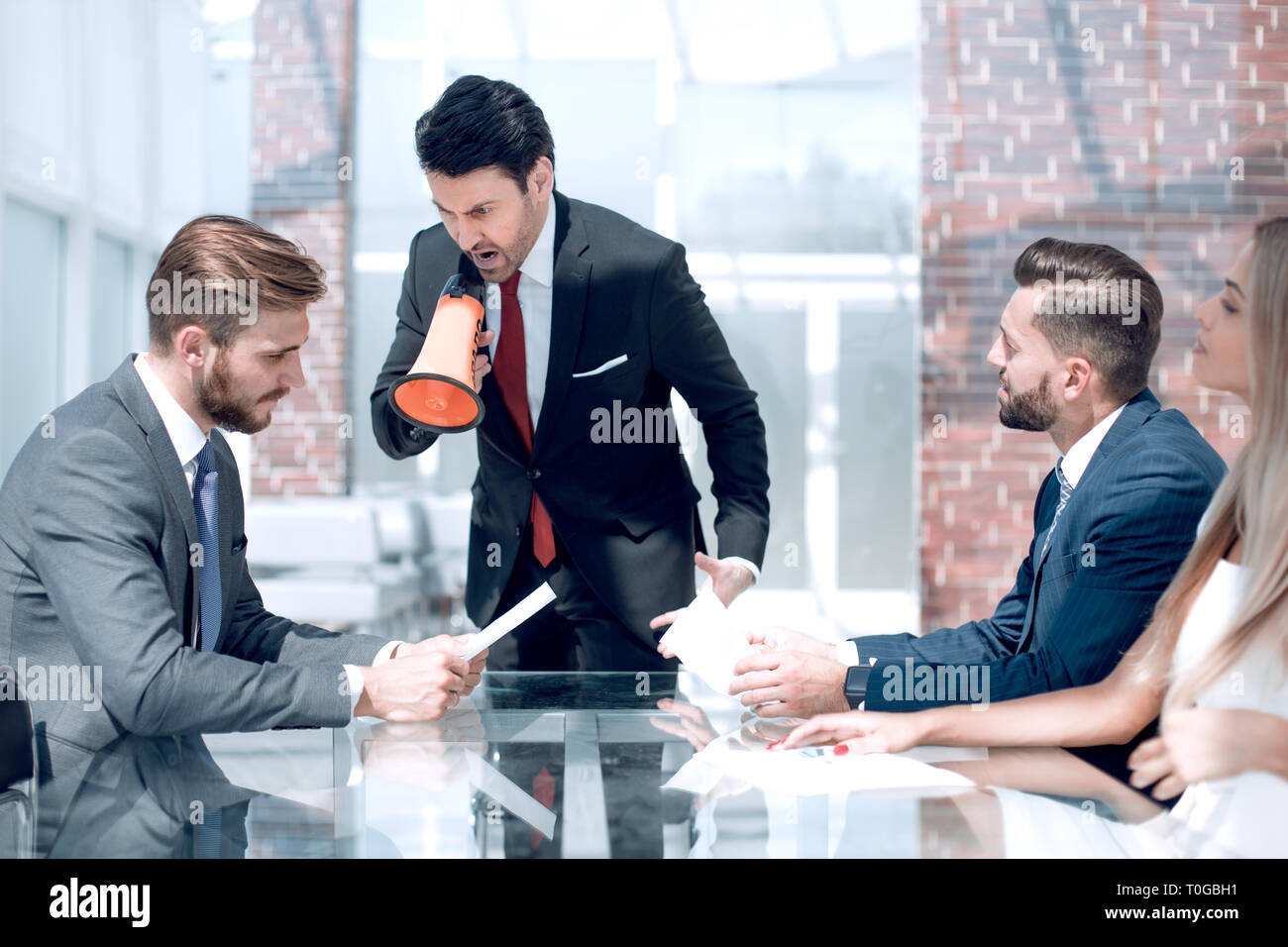 businessman with a megaphone at a meeting with the business team - Stock Image