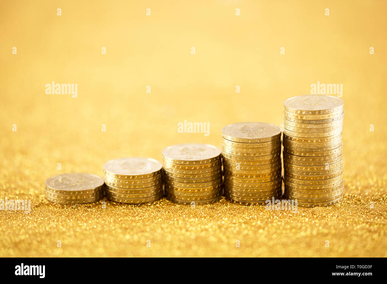 Rising golden coins - Stock Image