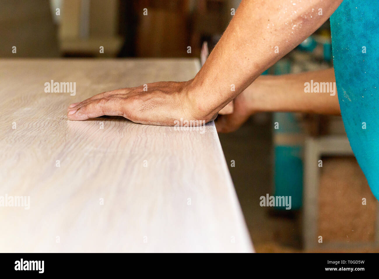 Male carpenter hands sanding the edge of a table manually, indoors. - Stock Image