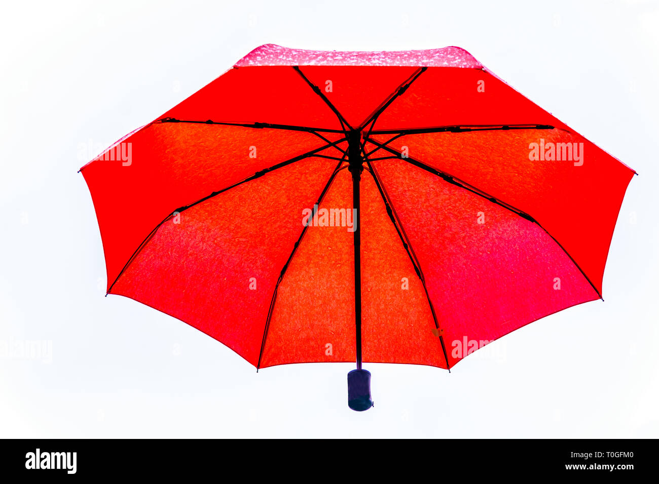 Red Umbrella floating in the air under cloudy sky - Stock Image