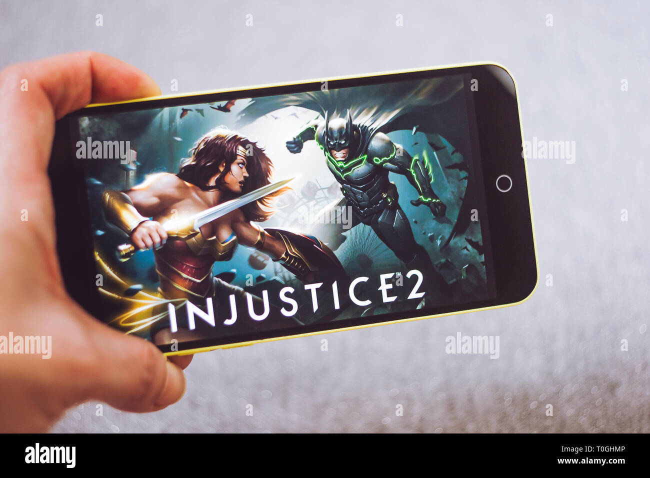 Berdyansk, Ukraine - March 4, 2019: Hands holding a smartphone with Injustice 2 game on display screen. - Stock Image
