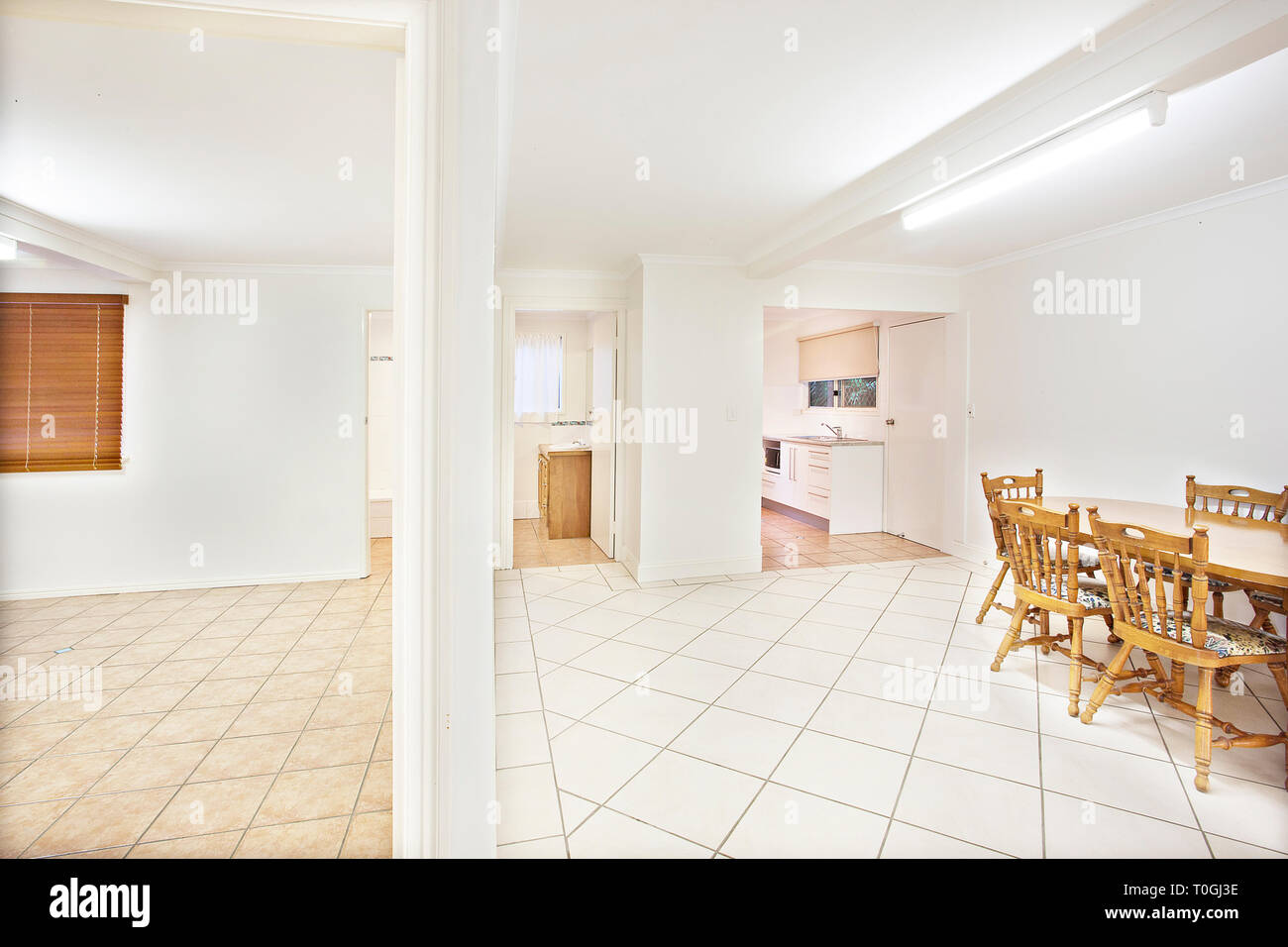 Bright white clean home interior with minimalist decor and a view down a iding wall to an empty tiled room and dining area with table and chairs & Bright white clean home interior with minimalist decor and a view ...