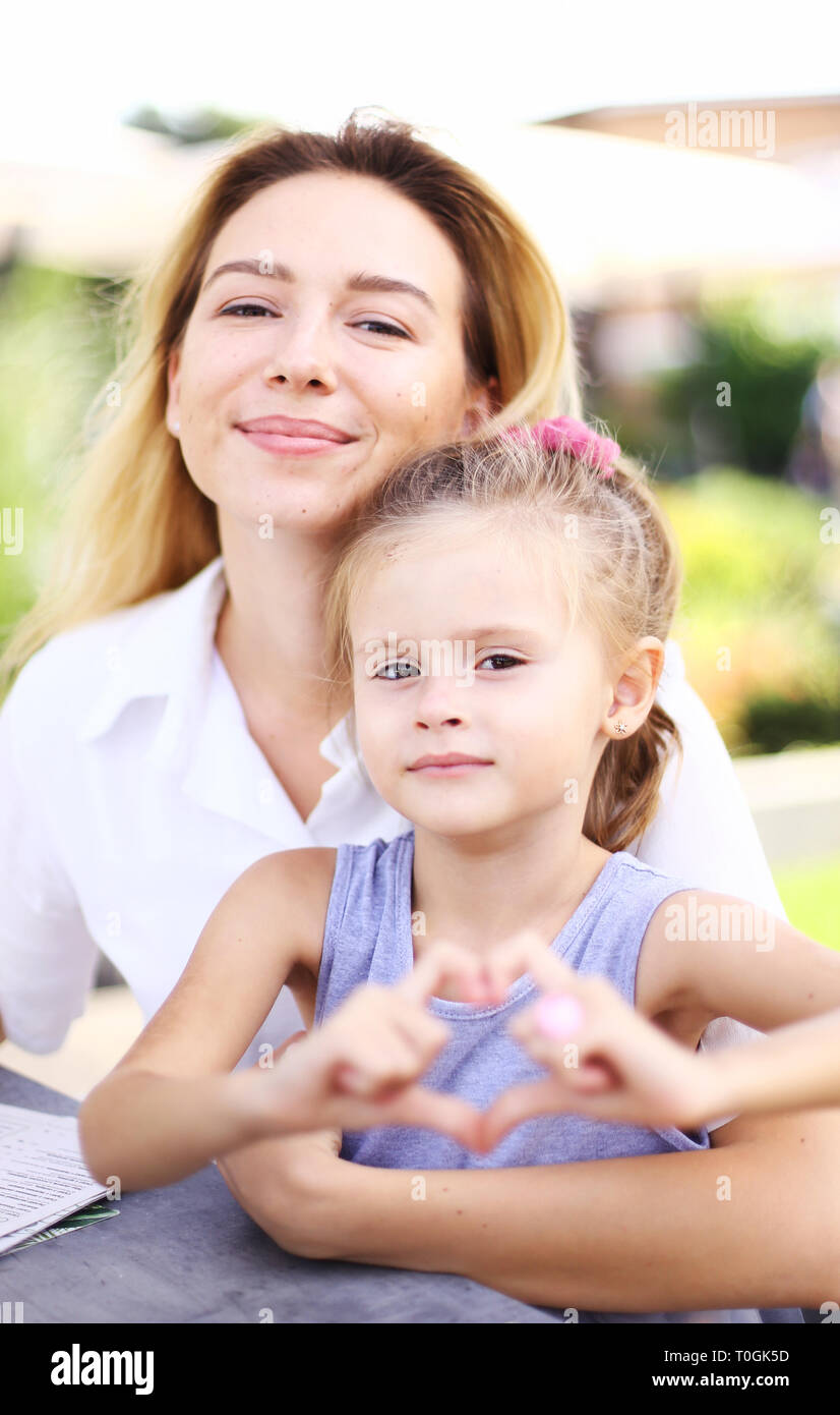 Young mother sitting with little daughter showing heart gesture. - Stock Image