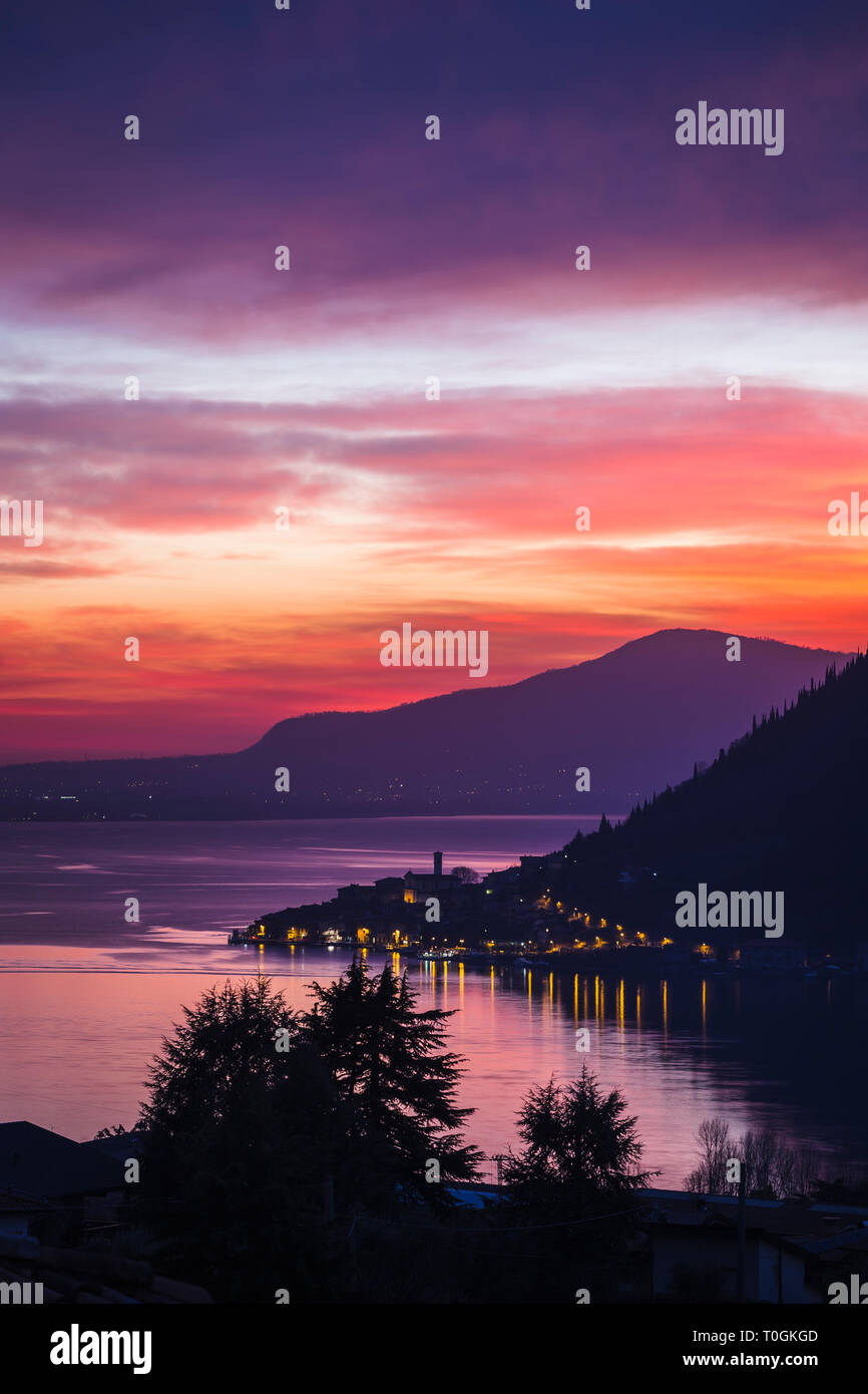 Lake Iseo at sunset with the town of Peschiera Maraglio on Monte Isola, Lombardy, Italy - Stock Image